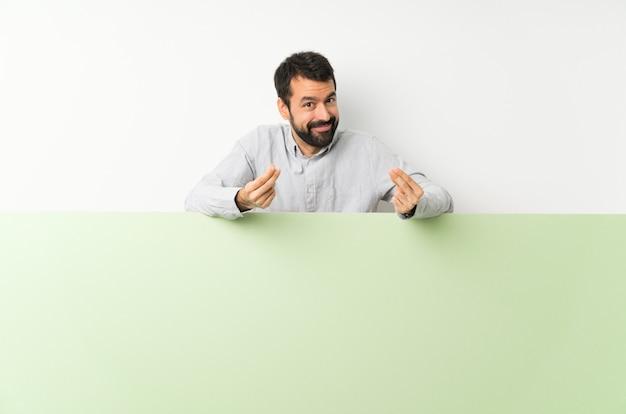 Jonge knappe mens die met baard een groot groen leeg aanplakbiljet houden die geldgebaar maken Premium Foto
