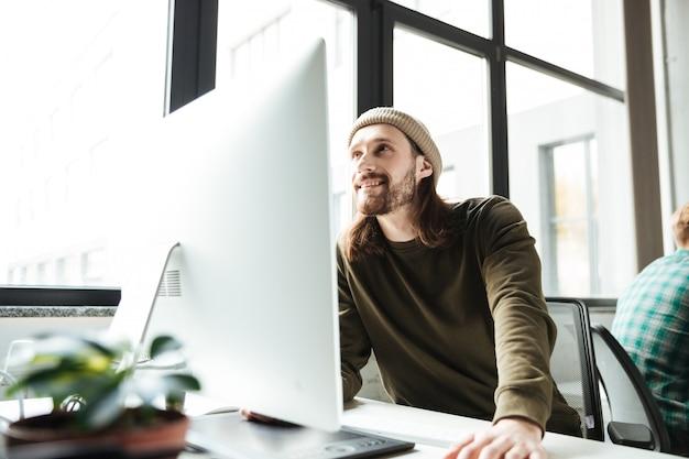 Jonge knappe mens in bureau die computer met behulp van Gratis Foto