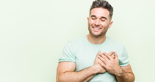 Jonge knappe mens tegen een groene muur die houdend handen op hart lachen, concept geluk. Premium Foto