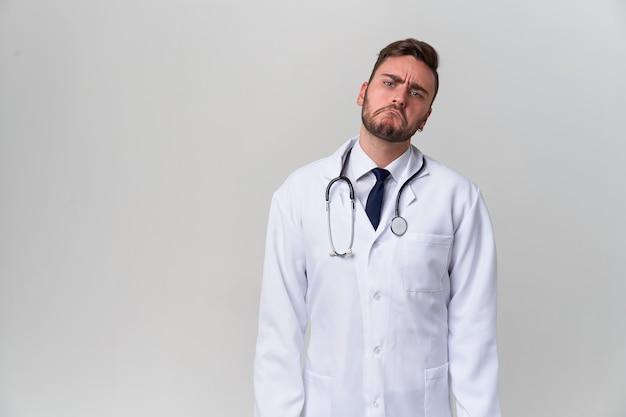 Jonge knappe moderne arts in een witte medische jurk staat in de studio op een wit. student-stagiair van een medische universiteit. Premium Foto
