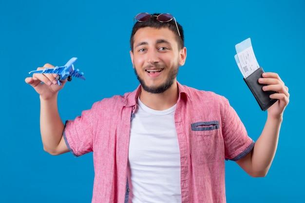 Jonge knappe reiziger kerel bedrijf speelgoed vliegtuig en vliegtickets kijken camera glimlachend vrolijk met blij gezicht staande over blauwe achtergrond Gratis Foto