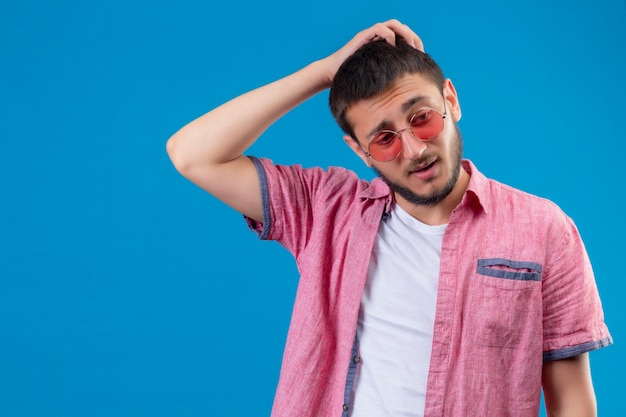 Jonge knappe reiziger kerel die zonnebril draagt ?? die zich met hand op hoofd voor fout bevindt onthoud fout slecht geheugenconcept dat zich over blauwe achtergrond bevindt Gratis Foto