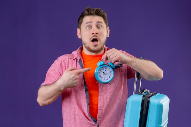 Jonge knappe reiziger man met blauwe koffer wijzend met vinger naar wekker in zijn andere hand Gratis Foto