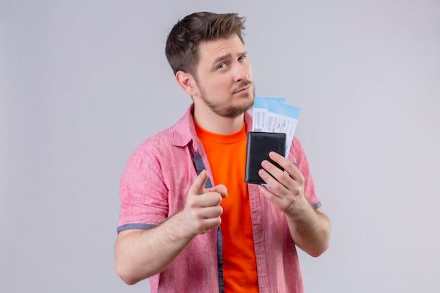Jonge knappe reiziger man met vliegtuigtickets wijzend met vinger naar camera met verdachte uitdrukking op gezicht staande over witte muur Gratis Foto