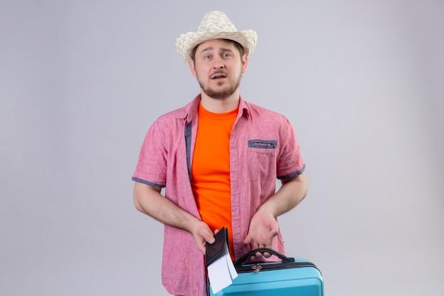 Jonge knappe reizigersmens die in zomerhoed blauwe koffer en vliegtuigtickets met droevige uitdrukking op gezicht houden die zich over witte muur bevinden Gratis Foto