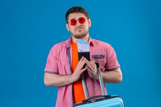 Jonge knappe reizigersmens die zonnebril draagt die vliegtuigtickets en koffer houdt Gratis Foto
