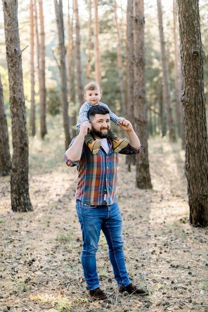 Jonge knappe vader en zoon, stijlvolle vrijetijdskleding dragen, plezier in herfst park Premium Foto