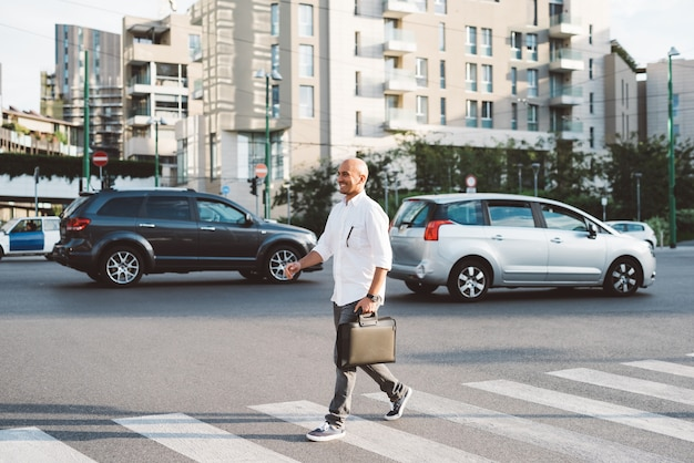 Jonge knappe zakenman die de straat kruist Premium Foto