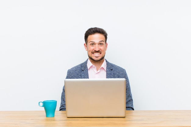 Jonge knappe zakenman die gelukkig en mal met een brede pret gekke glimlach en wijd open ogen kijkt Premium Foto