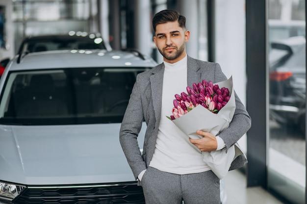 Jonge knappe zakenman leveren boeket van mooie bloemen Gratis Foto