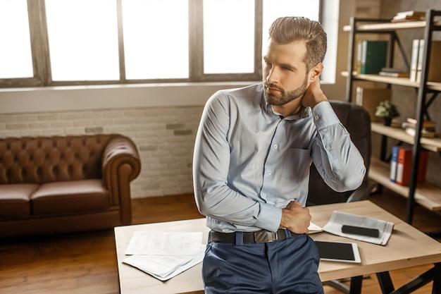 Jonge knappe zakenman poseren in zijn eigen kantoor. hij staat aan tafel en omhelst zichzelf. kerel kijkt naar de kant. telefoon en tablet met laptop op tafel achter. Premium Foto