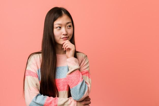 Jonge koele chinese vrouw die zijdelings met twijfelachtige en sceptische uitdrukking kijkt. Premium Foto