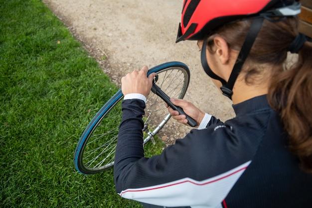 Jonge koele mannelijke fietser in sportkleding en beschermende helm repareren luchtkamer van fietswiel in park Premium Foto