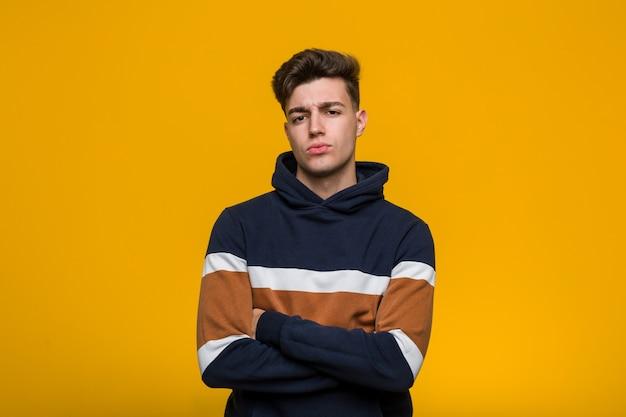 Jonge koele mens die hoodie het ongelukkige kijken dragen in camera met sarcastische uitdrukking. Premium Foto