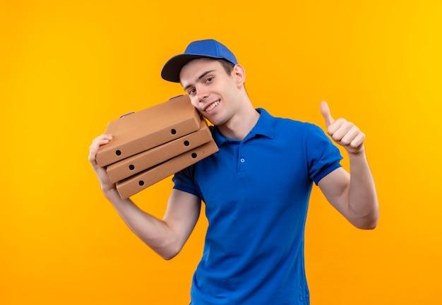 Jonge koerier die blauw uniform en blauwe pet draagt die gelukkige duimen omhoog doet en de zakken koestert Gratis Foto