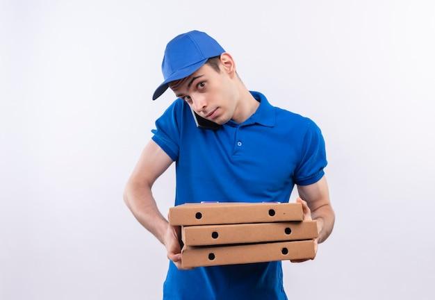 Jonge koerier die blauw uniform en blauwe pet draagt, houdt pizzadozen en praat over de telefoon Gratis Foto