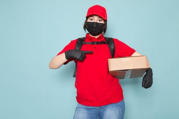 Jonge koerier in rode polo rode dop zwart steriel beschermend masker zwarte rugzak met pakket op blauw Gratis Foto