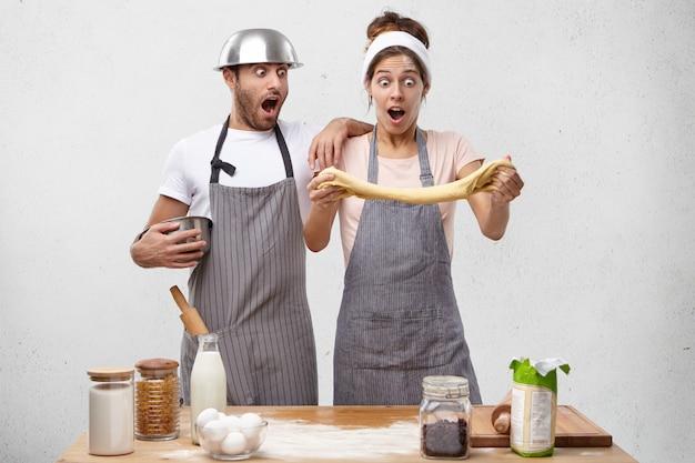 Jonge koks maken reclame voor goede gist, maken deeg, laten de geweldige resultaten zien: gebak is luchtig en elastisch Gratis Foto