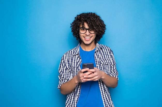Jonge krullende knappe mens die op de telefoon over geïsoleerd op blauwe muur typen Gratis Foto