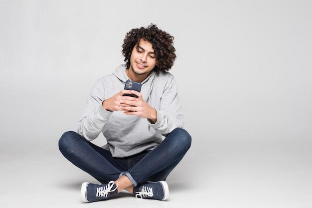 Jonge krullende mensenzitting op de vloer die een bericht verzendt dat op witte muur wordt geïsoleerd Gratis Foto