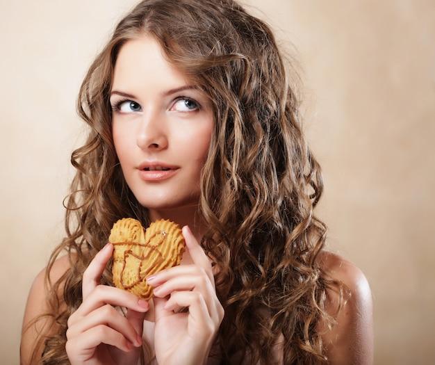 Jonge krullende vrouw met een cake Premium Foto