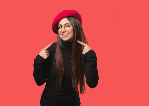 Jonge kunstenaar vrouw glimlacht, wijzend op mond Premium Foto