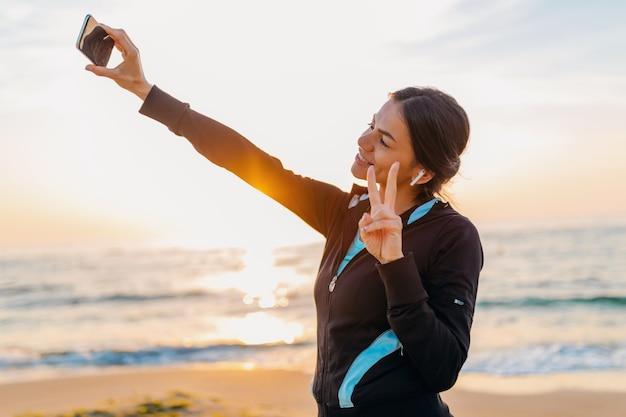 Jonge lachende aantrekkelijke slanke vrouw sport beoefening op ochtend zonsopgang strand in sportkleding, gezonde levensstijl, luisteren naar muziek op oortelefoons, selfie foto maken op telefoon in positieve stemming Gratis Foto