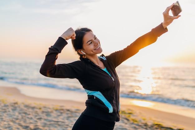 Jonge lachende aantrekkelijke slanke vrouw sport oefeningen doen op ochtend zonsopgang strand in sportkleding, gezonde levensstijl, luisteren naar muziek op oortelefoons, selfie foto op telefoon er sterk uitzien Gratis Foto