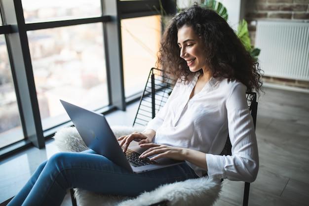 Jonge lachende brunette meisje zit op moderne stoel bij het raam in lichte, gezellige kamer thuis bezig met laptop in een ontspannen sfeer Premium Foto