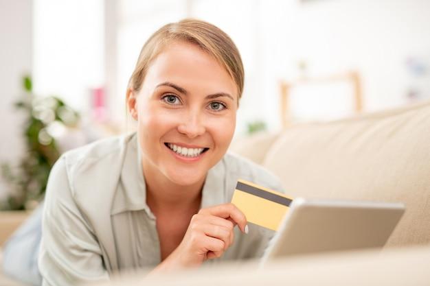 Jonge lachende online shopper met plastic kaart en touchpad bestellen terwijl liggend op de bank Premium Foto