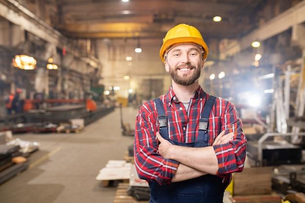 Jonge lachende professional in overall en beschermende helm poseren binnen grote industriële fabriek Premium Foto