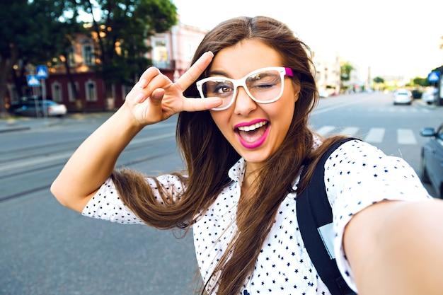 Jonge lachende tiener gelukkige vrouw selfie maken op straat, leng haren, lichte make-up en schattige heldere bril, alleen reizen, plezier, positieve stemming, vreugde, vakantie Gratis Foto