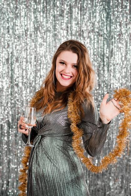 Jonge lachende vrouw met glas dichtbij klatergoud Gratis Foto