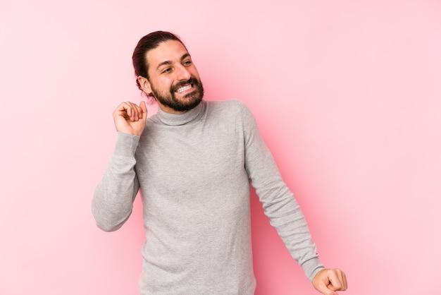Jonge lang haar man geïsoleerd op een roze ruimte dansen en plezier maken. Premium Foto