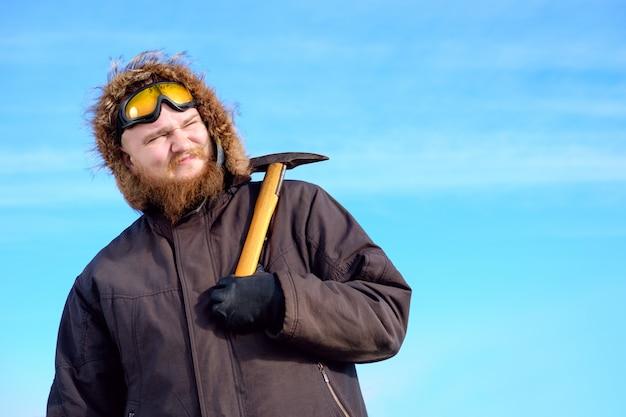 Jonge lange bebaarde polaire ontdekkingsreiziger met beschermende bril op het voorhoofd poseren met ijsbijl Premium Foto