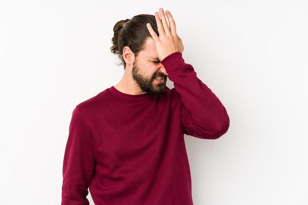 Jonge lange haarmens die op een witte muur wordt geïsoleerd die iets vergeet, voorhoofd met handpalm slaat en ogen sluit. Premium Foto