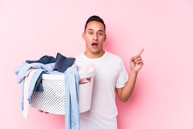 Jonge latijns-man oppakken van vuile kleren geïsoleerd wijzend naar de zijkant Premium Foto