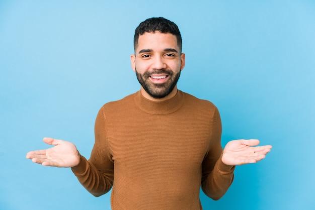 Jonge latijns-man tegen een blauwe achtergrond geïsoleerd met een welkome uitdrukking. Premium Foto