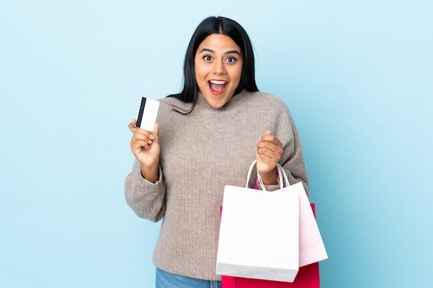 Jonge latijns-vrouw op blauwe muur boodschappentassen houden en verrast vrouw Premium Foto