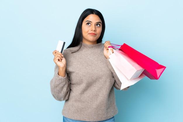 Jonge latijns-vrouw vrouw op blauwe muur houden boodschappentassen en een creditcard en denken Premium Foto