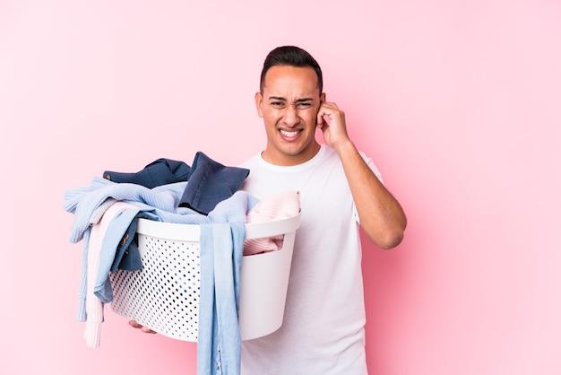 Jonge latijnse mens die vuile geïsoleerde kleren oppakt die oren met handen bedekken. Premium Foto