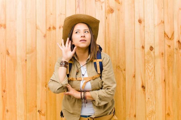 Jonge latijnse ontdekkingsreizigervrouw tegen houten muurachtergrond Premium Foto