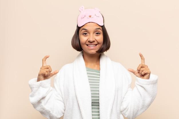 Jonge latijnse vrouw die eigen glimlach met beide handen omlijst of schetst, positief en gelukkig kijkt, wellnessconcept Premium Foto