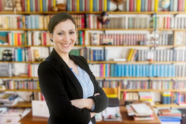 Jonge leraar die zich voor een boekenkast bevindt Premium Foto