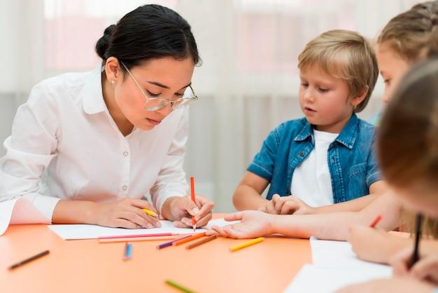 Jonge leraar doet haar klas met kinderen Gratis Foto