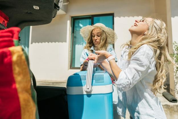 Jonge lesbische paar vakantie reis op de auto in zonnige dag voorbereiden. glimlachende en gelukkige meisjes voordat ze naar zee of oceaan gaan. concept van relatie, liefde, zomer, weekend, huwelijksreis, vakantie. Gratis Foto