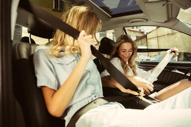 Jonge lesbische paar vakantie reis op de auto in zonnige dag voorbereiden. vrouwen zitten en klaar om naar zee, rivier of oceaan te gaan. concept van relatie, liefde, zomer, weekend, huwelijksreis. Gratis Foto