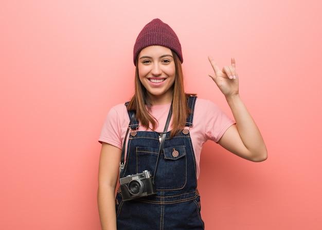 Jonge leuke fotograafvrouw die een rotsgebaar doet Premium Foto
