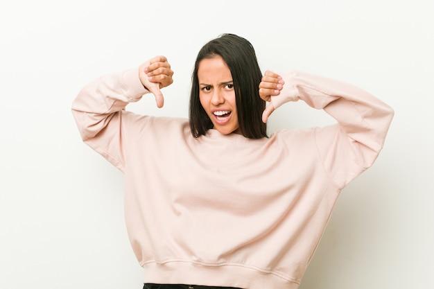 Jonge leuke spaanse tienervrouw die duim tonen en afkeer uitdrukken. Premium Foto