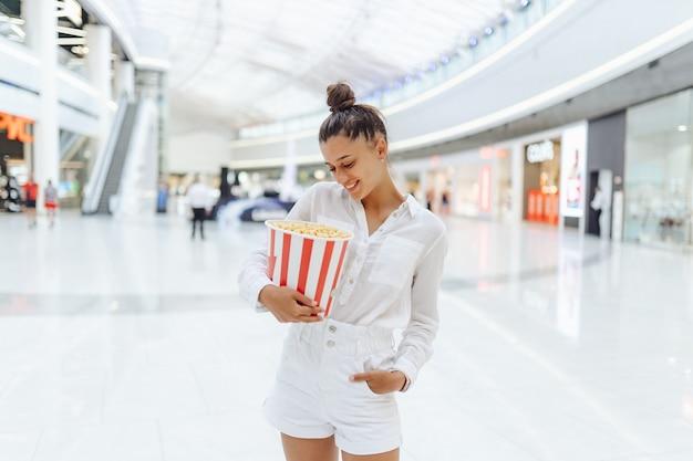 Jonge leuke vrouw met popcorn op de achtergrond van het winkelcentrum Gratis Foto